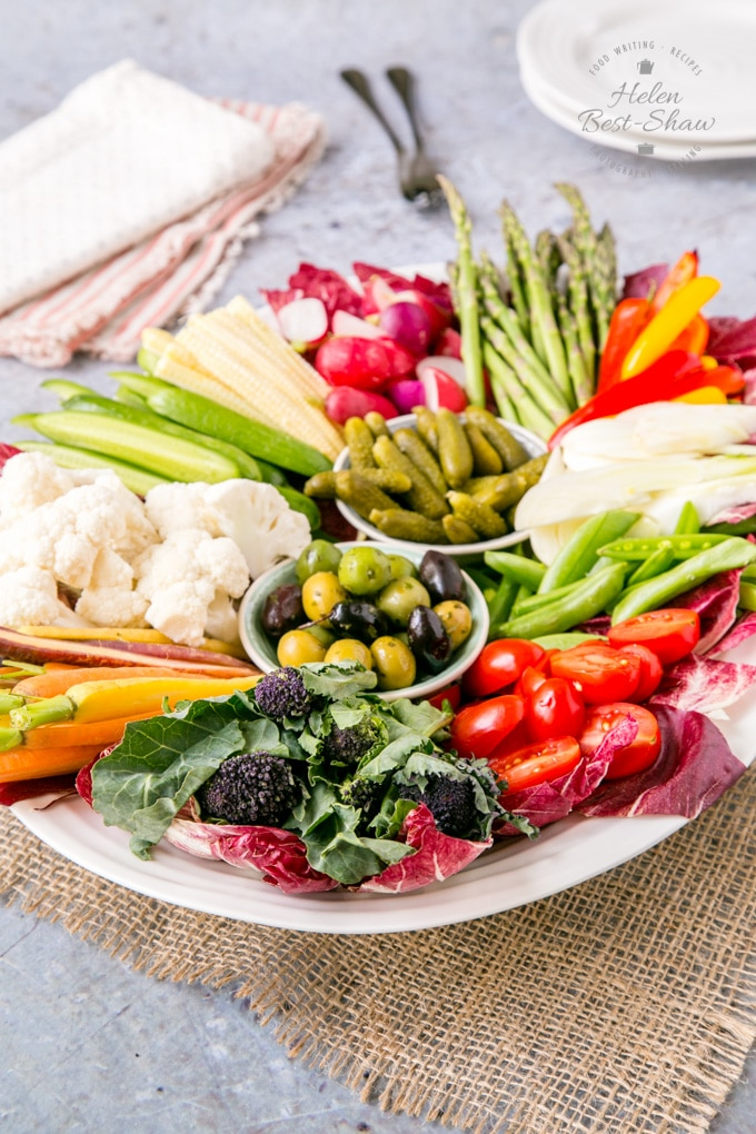 A white oval platter covered with various raw vegetable crudités.