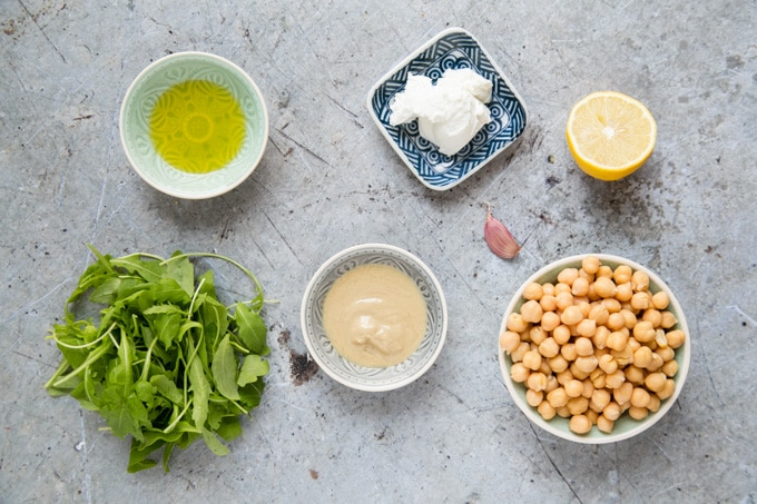 A top down view of the ingredients for goats cheese and rocket hummus. Chick peas, tahini, olive oil, soft goats cheese, half a lemon and a handful of rocket.