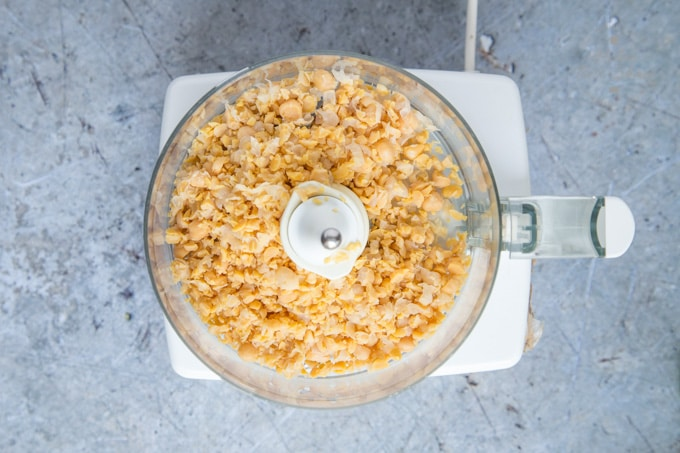 A top down view of a food processor holding chick peas that have been blitzed.