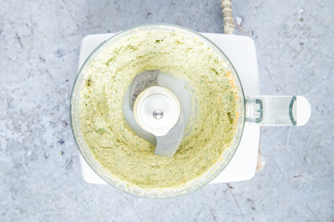 A top down view of goat's cheese and rocket hummus, in a food processor, fully blitzed and ready to be served.