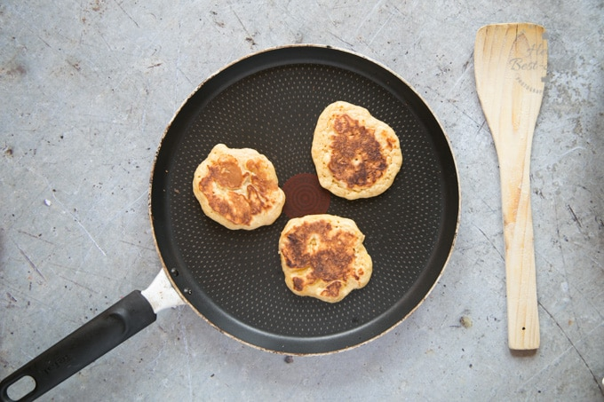 A top down picture of making mango pancakes. Once one side of the pancakes has cooked, they're flipped to cook the other. This picture shows the cooked bottom coloured light brown.