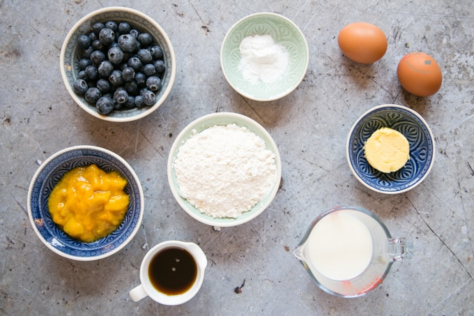 The ingredients for mango pancakes ins small bowls and jugs: blueberries, baking powder, eggs, butter, milk, flour, maple syrup and mango puree.