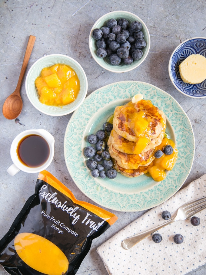 A top down picture of mango pancakes served on a green plate, garnished with blueberries, syrup and mango puree. Next to the plate are dishes of butter, blueberries, mango puree, maple syrup and a packet of Exclusively Fruit Pure Fruit Compote Mango.