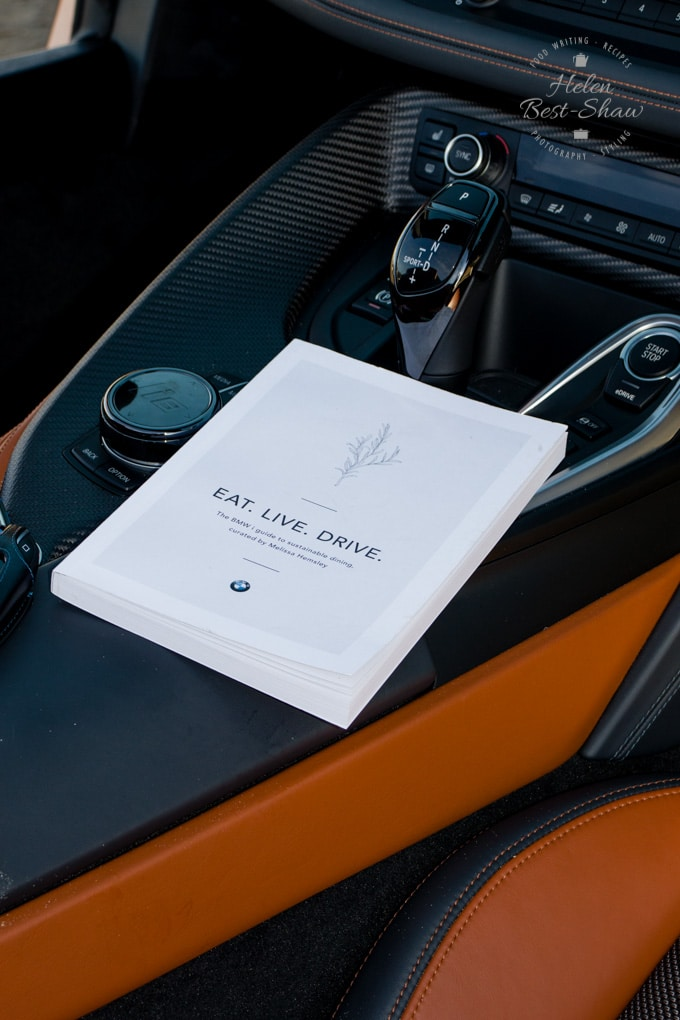 "A picture of the centre console of a BMW i8 roadster, with a copy of ""Eat, Live, Drive"" sitting next to the gear lever."