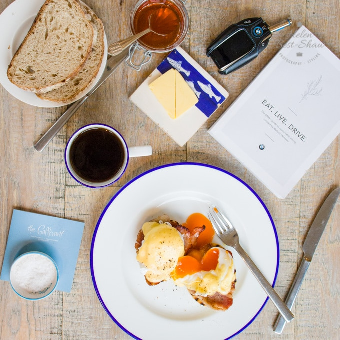 "A top down view of breakfast: eggs benedict, with vibrant orange egg yolks oozing onto a white plate. Bread, coffee, butter and marmalade are also seen. A copy of ""Eat, Live, Drive"" and a BMW car key lie on the tabletop."