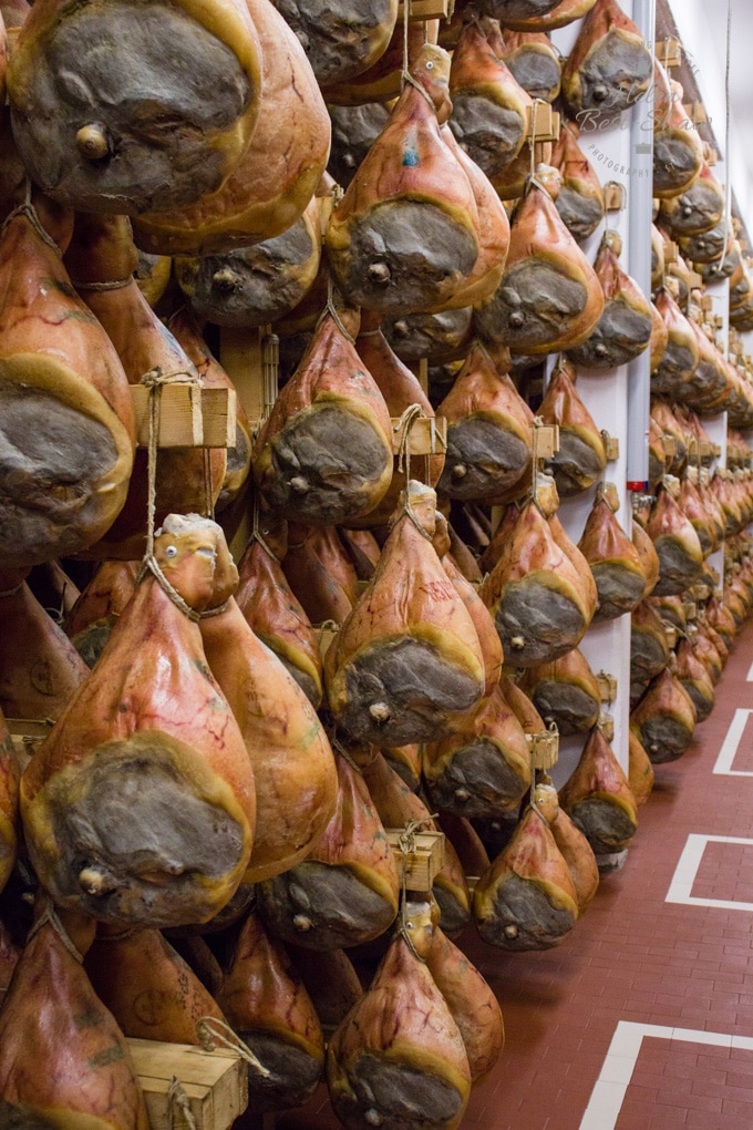 Rows of parma hams hanging from wooden frames waiting for their quality inspection