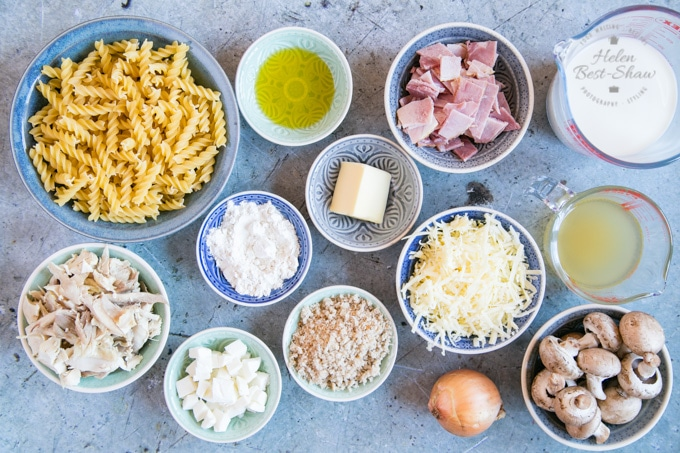 The ingredients for turkey and ham pasta bake, arranged in small bowls and dishes.