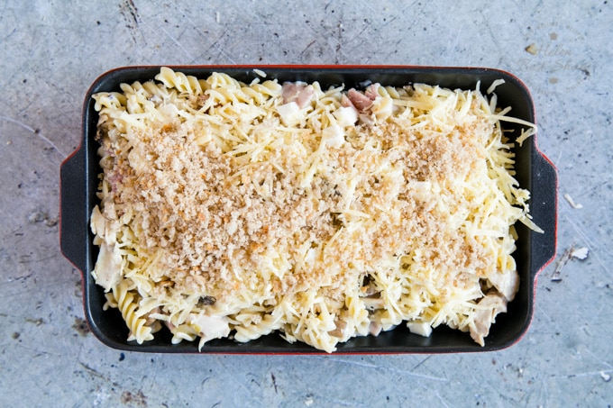 A top down view of a black rectangular dish full of turkey and ham pasta bake. The dish has been covered with breadcrumbs and cheese, and is ready to be baked in the oven.
