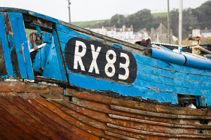 A close up on the rear quarter of an abandoned fishing boat, in Hastings. The number RX 83 in a black oval cartouche is clearly painted on the blue topsides. The paint is peeling, and the boat is rotting.
