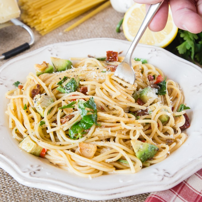 A bowl of easy anchovy pasta with chilli. A fork is twisting the spaghetti.