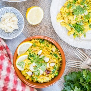 A closeup of leftover roast turkey biryani. The vibrant yellow turkey and rice dish is in a shallow brown bowl, garnished with a slice of lemon, slivered almonds and coriander leaves. In the background is a white plate on which more curry has been served.