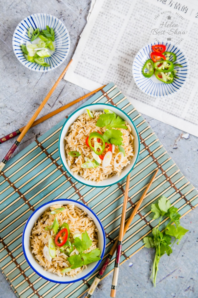 A top down shot of two blue and white china bowls filled with Chinese style rice that has been cooked in the Instant Pot. The rice is garnished with sliced chillis and spring onion and fresh coriander. There are a pair of chopsticks next to the bowl and some fresh chilies in the background