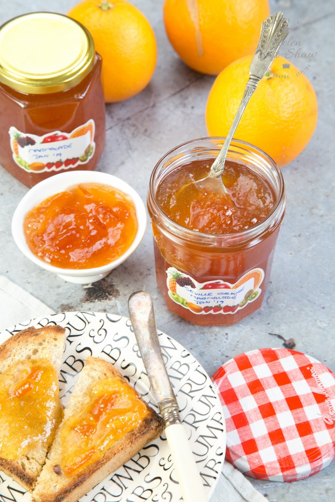 A picture of two pots of Seville orange marmalade, a plate holding a slice of toast with butter and marmalade, and three oranges.