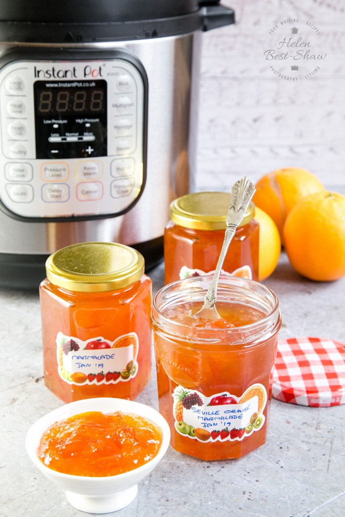 Three pots of Seville orange marmalade, and a small marmalade filled dish in the foreground, In the background is an Instant Pot electric pressure cooker.