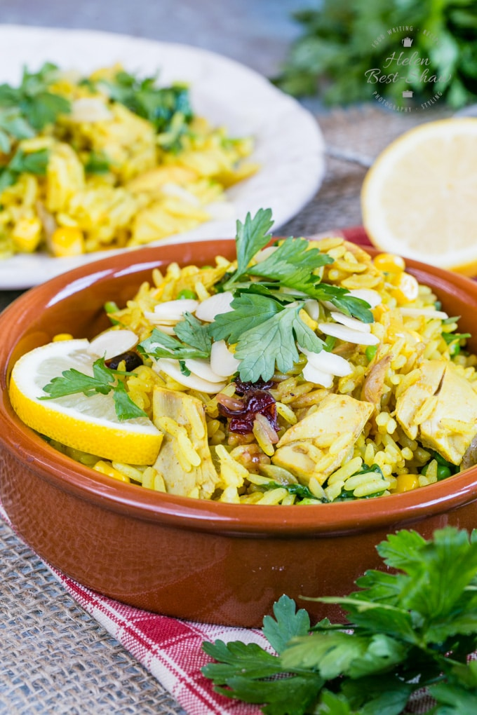 A closeup of leftover roast chicken biryani. The vibrant yellow chicken and rice dish is in a shallow brown bowl, garnished with a slice of lemon, slivered almonds and coriander leaves. In the background is a white plate on which more curry has been served.