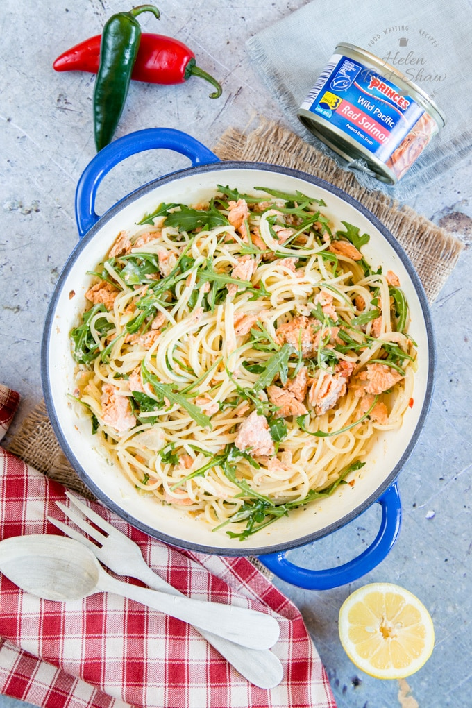 A top down picture of a dish of 10 minute creamy salmon pasta. Surrounding the dish is a tin of wild Alaskan salmon, two chilis, a wooden spoon and fork, and half a lemon.