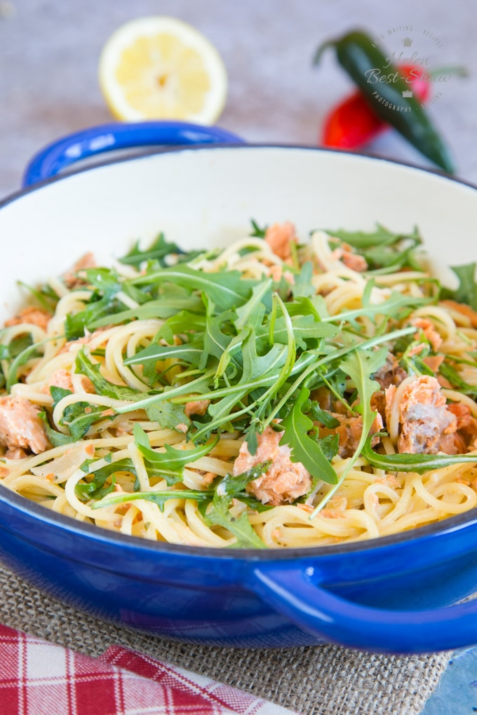 A picture of a blue shallow dish holding 10 minute creamy salmon pasta, ready to serve.