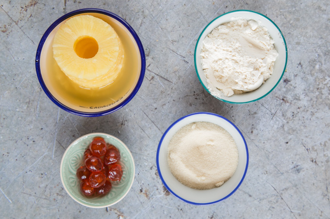 A top down view of the ingredients to make a pineapple upside down cake. 4 bowls containing, canned pineapple rings, glace cherries, self-raising flour and sugar
