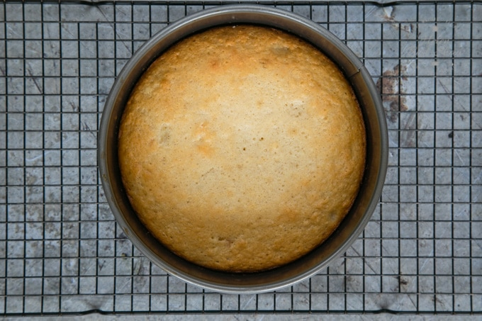 A top down view of a freshly cooked pineapple upside down cake in a circulr pan, standing on a cooling rack