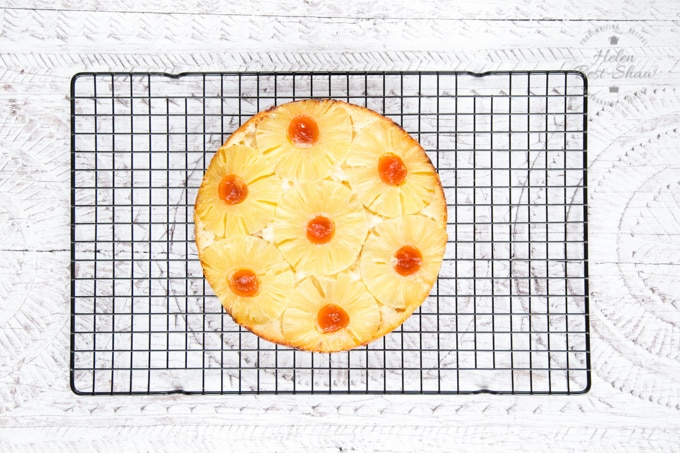 A top down photo of a pineapple upside down cake on a wire cooling rack