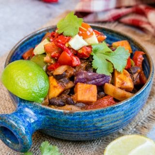A close up of a blue bowl full of Brazilian roasted vegetable feijoada. A wedge of lime and leaves of coriander garnish the dish.