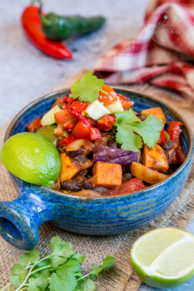 A bowl full of Brazilian roasted vegetable feijoada, garnised with coriander leaves and a wedge of lime. Around the bowl are a red and green chilli, a cloth, half a lime and some more coriander leaves.