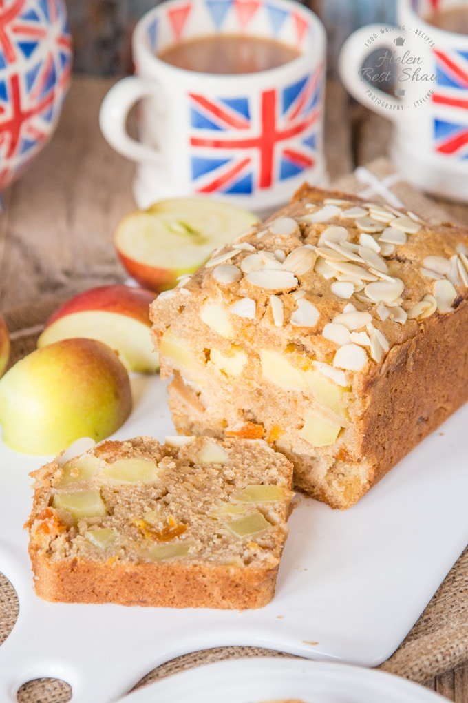 A dorset apple cake on a white porcelain board. The cake has been sliced open to show chunks of apple inside.