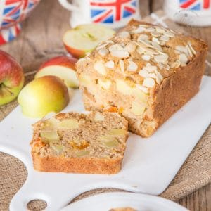 A Dorset apple cake surrounded by quartered apples.