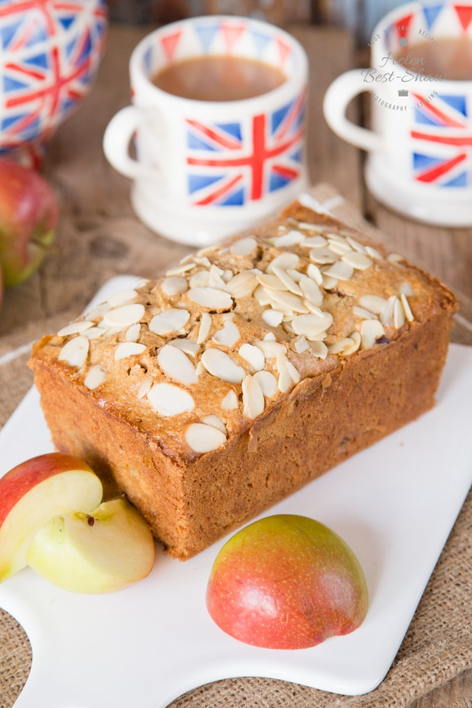 Dorset apple cake on a white porcelain board. The cake is surrounded by cups of tea and halved apples. The cake itself has been topped with sliced almonds.