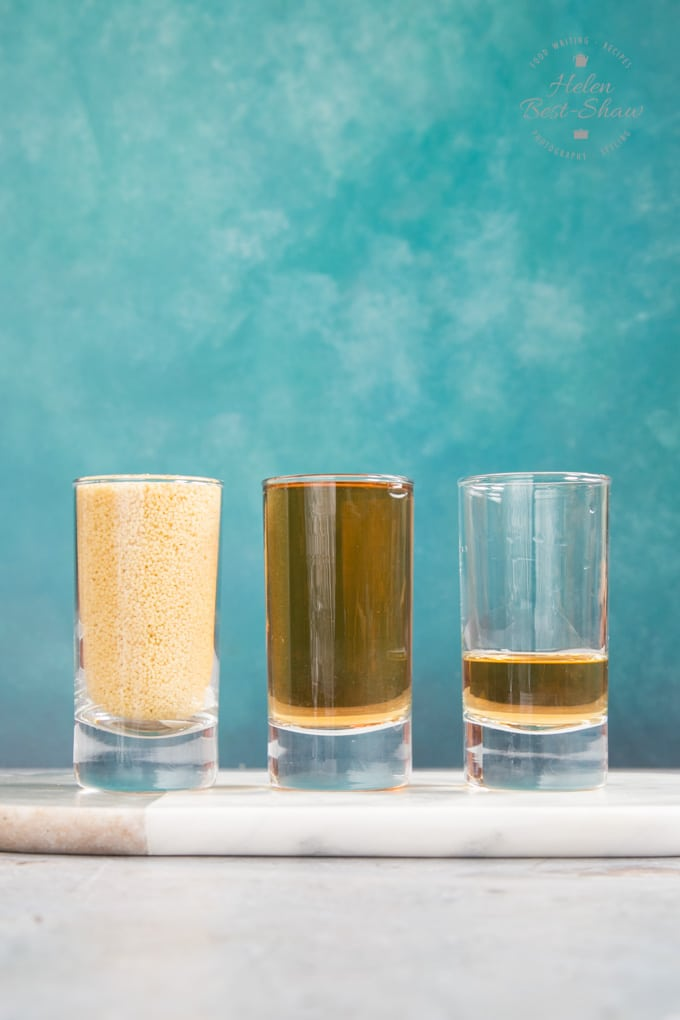Cooking cous cous - measuring by volume. A shot glass of cous cous and two shot glasses of vegetable stock, one full to the brim, and the other one quarter full.