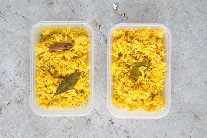 A top down picture of two take-away trays of yellow easy Instant Pot pilau rice. Each tray is garnished with a bay leaf.