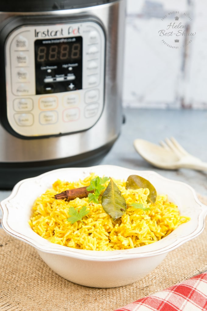 A bowl of yellow easy Instant Pot pilau rice. In the background is an Instant Pot electric pressure cooker.