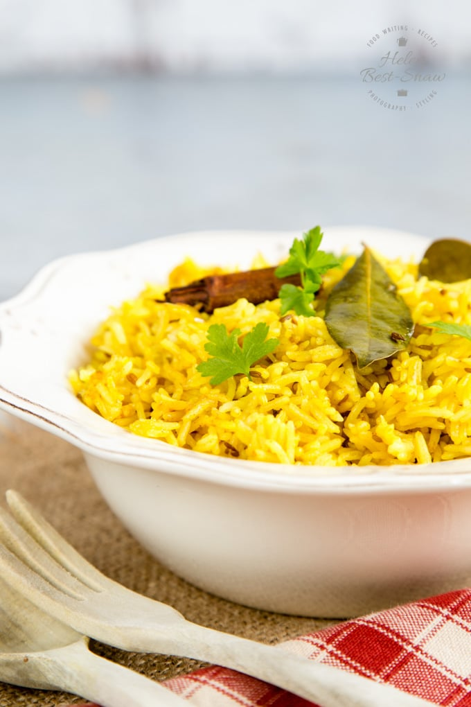A close up on a bowl of yellow easy Instant Pot pilau rice. The rice is garnished with fresh parsley, a bay leaf and a small stick of cinnamon.