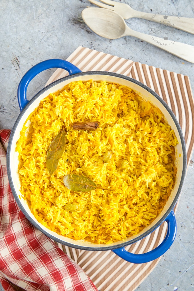 A top down photo of a casserole dish containing vibrant yellow home-made pilau rice. There are some cardamom pods, a stick of cinnamon and a bay leaf in the rice