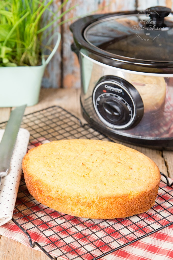 A picture of cornbread on a cooling rack, in front of a slow cooker/crockpot.