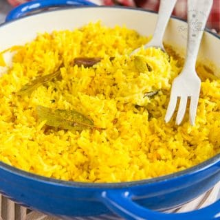 a casserole dish containing vibrant yellow home-made pilau rice. There are some cardamom pods, a stick of cinnamon and a bay leaf in the rice