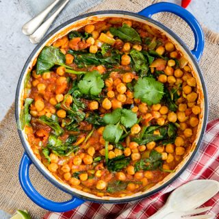 A square photo of a blue casserole dish filled with Indian chickpea curry with tomato and spinach. The round casserole dish fills the picture.
