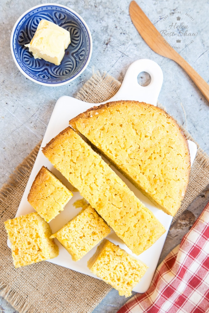 A top down shot of slow cooker cornbread on a white porcelain board. A small dish of butter sits next to the bread, as well as a wooden butterknife. Half the cornbread has been cut into squares.