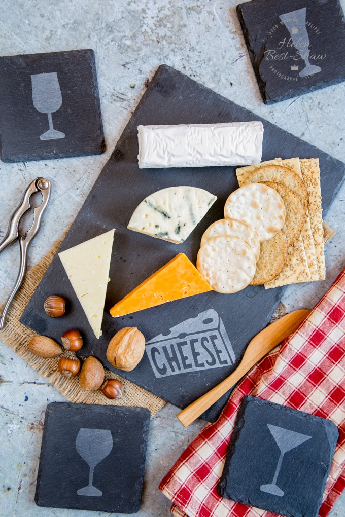 A lifestyle photo of an etched slate cheeseboard covered wtih a selection of cheeses