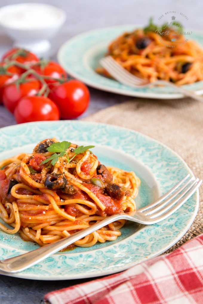 Rich red spaghetti puttanesca on a pale green plate.