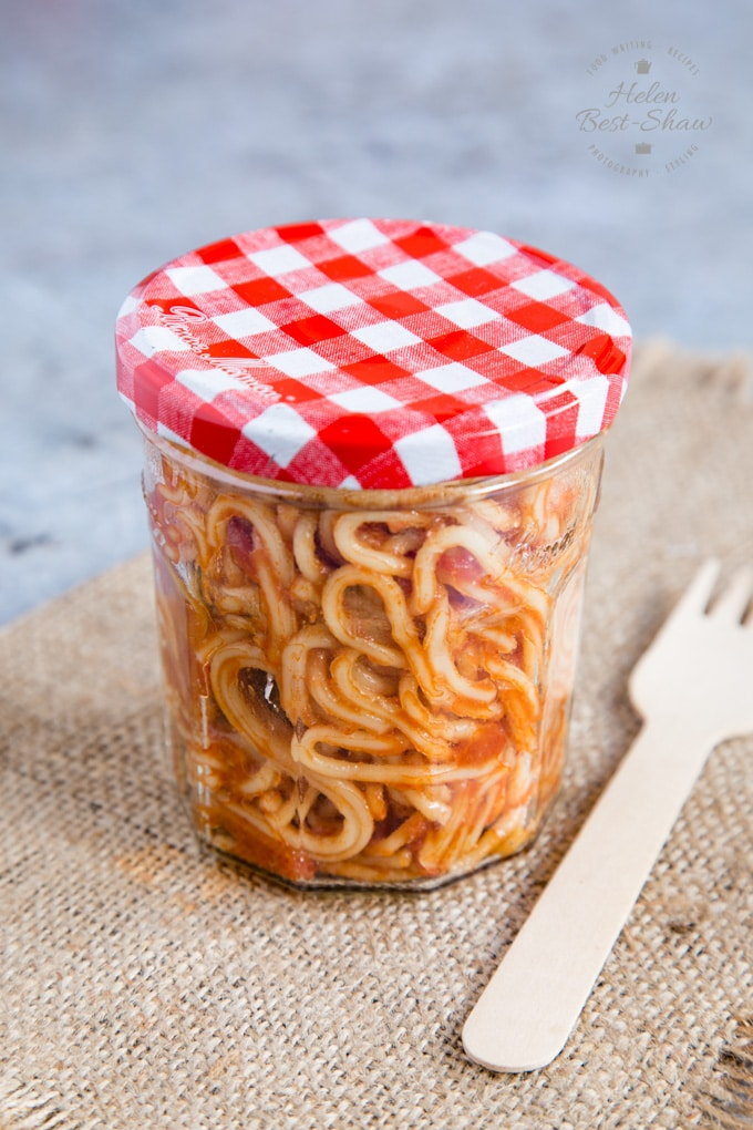 A jam jar of pasta puttanesca, ready for a grab and go lunch.