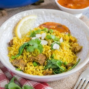 A close up of a bowl of yellow leftover lamb biryani with green spinach and parsley.