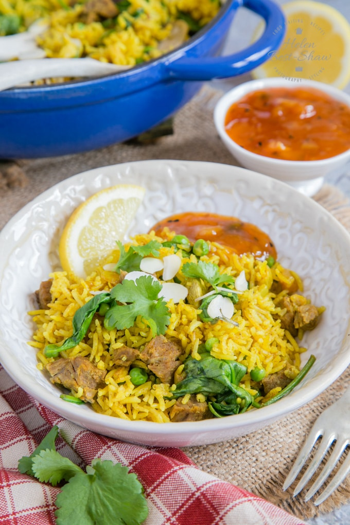 A bowl of vibrant yellow leftover lamb biryani, with an orange mango chutney garnish.