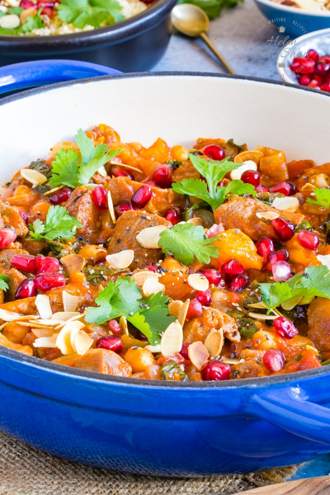 A flat blue casserole dish of leftover lamb tagine with apricot, garnished with almonds, coriander and