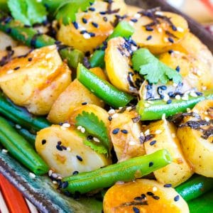 A close up of Japanese potato salad with French beans and black and white sesame seeds.