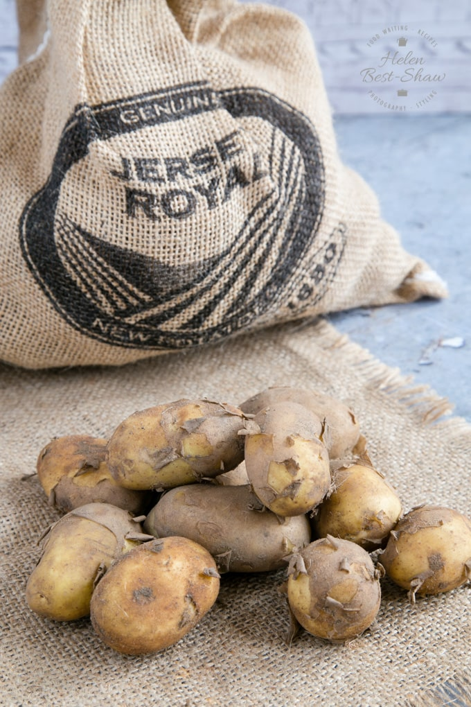A hessian sack and pile of muddy Jersey Royal new potatoes