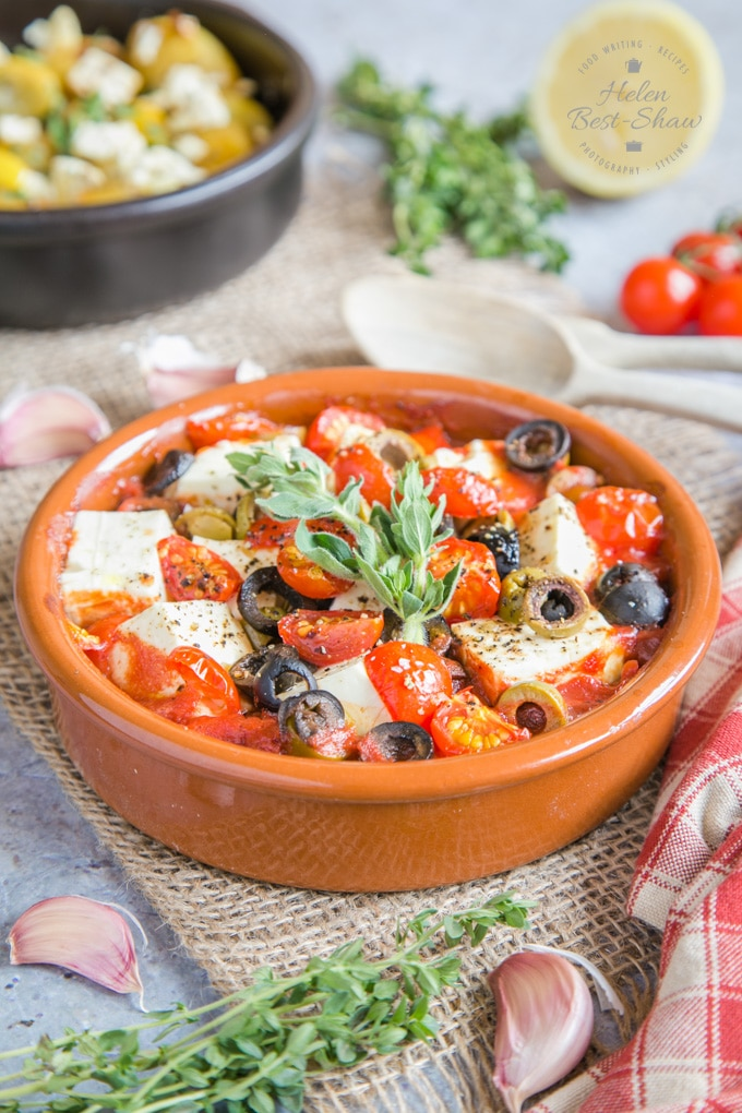 A dish of baked feta and tomatoes, garnished with fresh herbs.