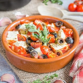 A close up of a dish of baked feta and tomatoes.