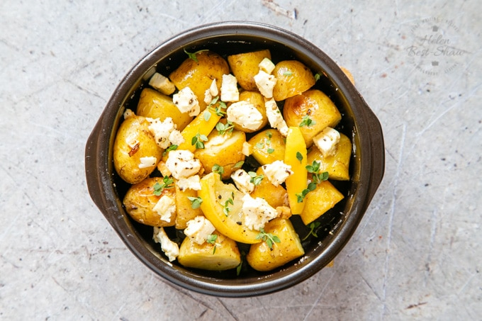 Greek potatoes with lemon and feta ready to serve, in a circular black dish.