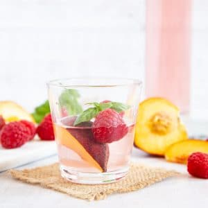 A glass of peach gin, garnished with peach and raspberry
